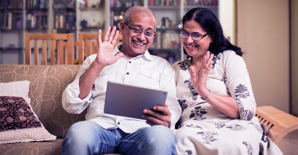 A couple video chatting loved ones on a tablet